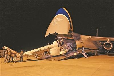 图:中国首支维和直升机分队先遣组人员将直升机搬运上联合国安排的安-124运输机。陈凯摄